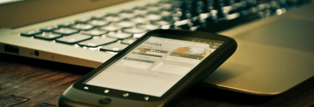 A smartphone beside a laptop